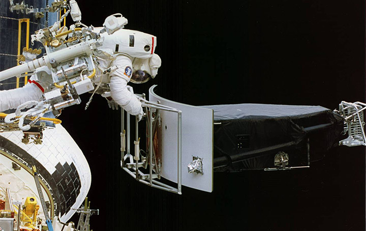 Astronaut Jeffrey Hoffman pulls Hubble's original wide-field camera out of the telescope during the first space shuttle servicing mission in December 1993. Credit: NASA