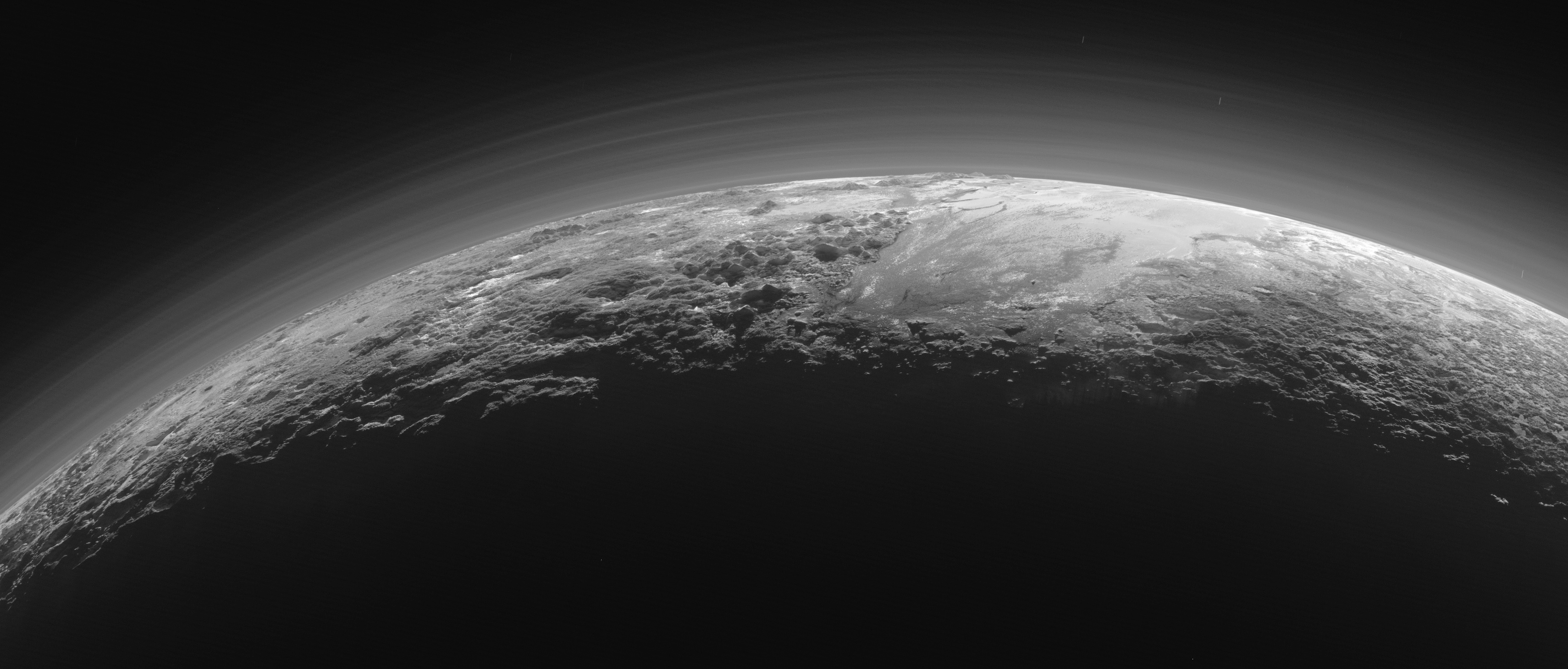 Just 15 minutes after its closest approach to Pluto on July 14, 2015, NASA's New Horizons spacecraft looked back toward the sun and captured this near-sunset view of the rugged, icy mountains and flat ice plains extending to Pluto's horizon. The smooth expanse of the informally named icy plain Sputnik Planum (right) is flanked to the west (left) by rugged mountains up to 11,000 feet (3,500 meters) high, including the informally named Norgay Montes in the foreground and Hillary Montes on the skyline. To the right, east of Sputnik, rougher terrain is cut by apparent glaciers. The backlighting highlights more than a dozen layers of haze in Pluto's tenuous but distended atmosphere. The image was taken from a distance of 11,000 miles (18,000 kilometers) to Pluto; the scene is 780 miles (1,250 kilometers) wide. Credit: NASA/Johns Hopkins University Applied Physics Laboratory/Southwest Research Institute