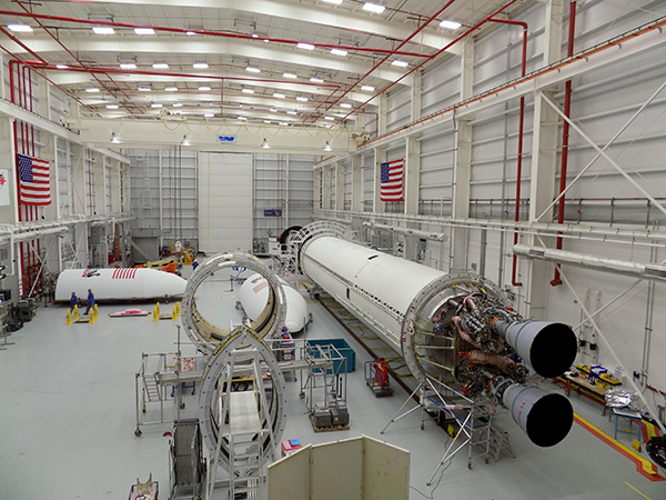 Work inside Orbital ATK's horizontal integration facility at the Wallops launch site targets a hotfire of the twin-engine Antares rocket with RD-181 engines in early 2016. This picture shows the first two RD-181 engines integrated with the Antares booster. Credit: Orbital ATK