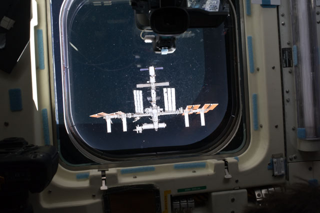 The International Space Station, seen here through the window of space shuttle Endeavour in 2011, is the largest spacecraft ever to fly in space. Credit: NASA