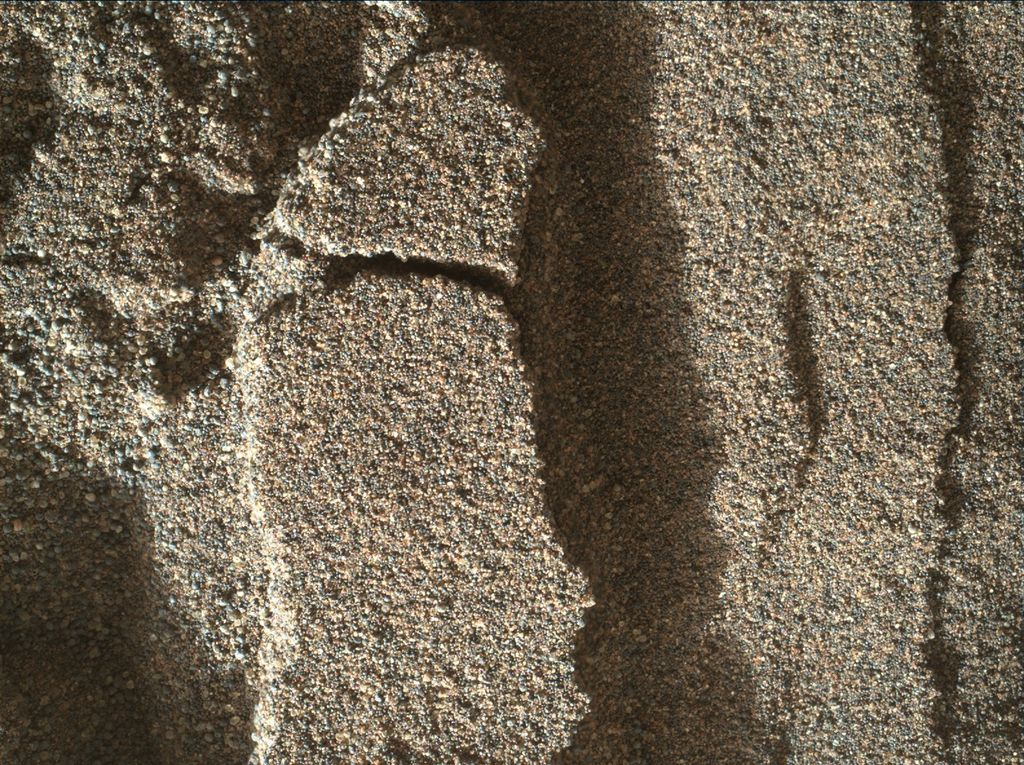 This view shows grains of sand where NASA's Curiosity Mars rover was driven into a shallow sand sheet near a large dune. The disturbance by the wheel exposed interior material of the sand body, including finer sand grains than on the undisturbed surface. Sunlight is coming from the left. The scene covers an area 1.3 inches by 1.0 inch (3.3 by 2.5 centimeters). This is a focus-merge product from Curiosity's Mars Hand Lens Imager (MAHLI), combining multiple images taken at different focus settings to yield sharper focus at varying distances from the lens. The component images were taken on Dec. 3, 2015, during the 1,182nd Martian day, or sol, of Curiosity's work on Mars. Credit: NASA/JPL-Caltech/MSSS