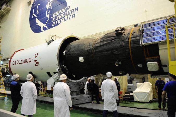 Russian technicians enclose the Progress MS-02 spacecraft inside the Soyuz rocket's payload fairing. Credit: Roscosmos