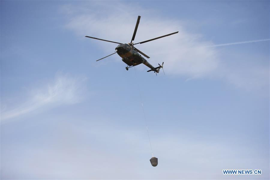 A helicopter hoists the Shijian 10 landing capsule after its return to Earth on Monday. Credit: Xinhua/Chen Junqing