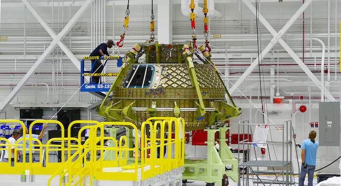 Boeing employees connect the upper and lower domes of the pressure shell for the CST-100 Starliner structural test article. Credit: Boeing