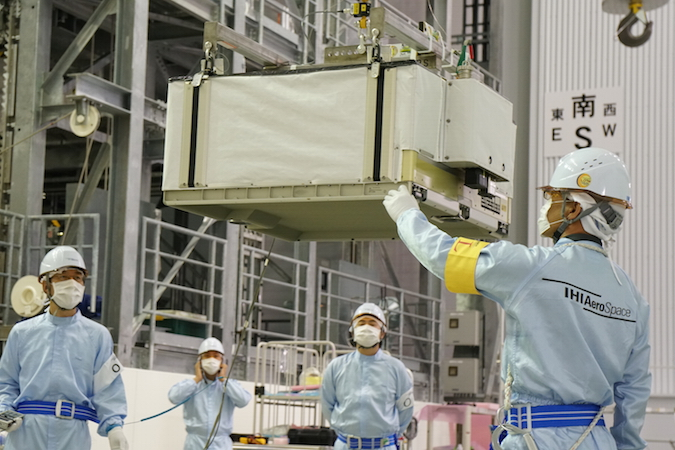 Technicians lift one of the six lithium-ion batteries set to launch Sept. 30 for installation into the HTV's exposed pallet. Credit: JAXA