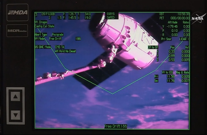 This view of a television monitor on the space station shows an overlay seen by astronauts as the Dragon cargo capsule approached the complex. Credit: NASA TV/Spaceflight Now