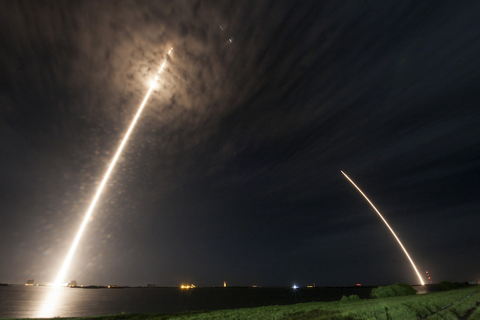 In this long exposure photo, the Falcon 9 rocket streaks away from the Complex 40 launch pad at left, then its first stage booster returns to landing at right a few miles away. Credit: SpaceX