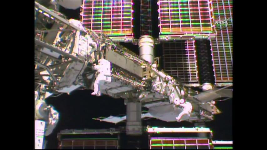 Spacewalkers Jeff Williams and Kate Rubins are dwarfed by the International Space Station's truss backbone during Thursday's EVA. Credit: NASA TV