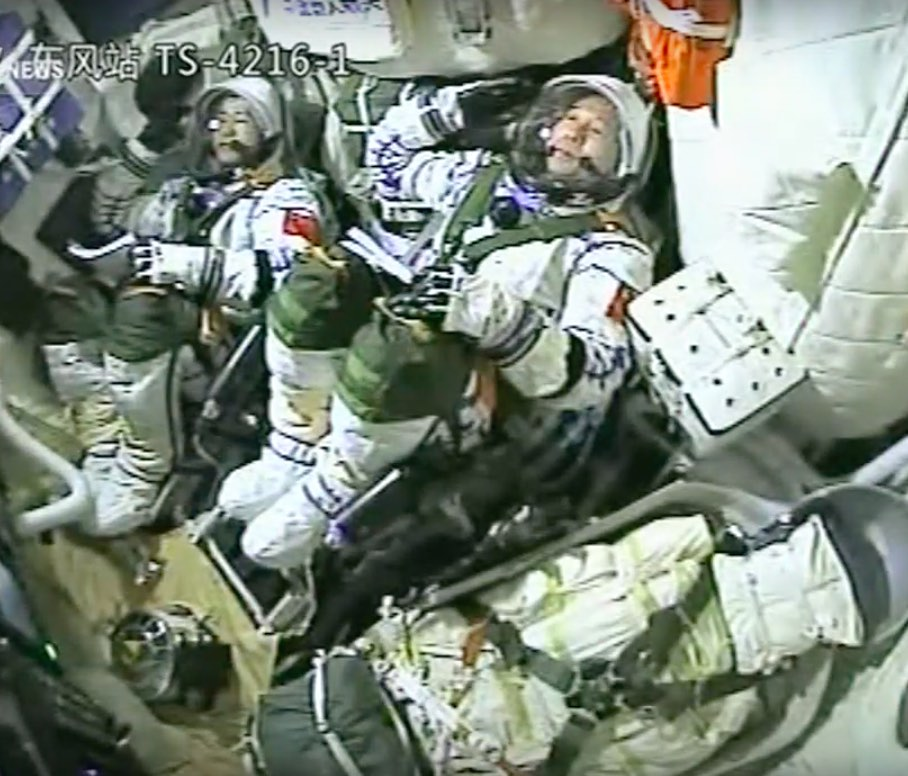 Astronauts Chen Dong (left) and Jing Haipeng (right) give a salute moments before launch. Credit: CCTV